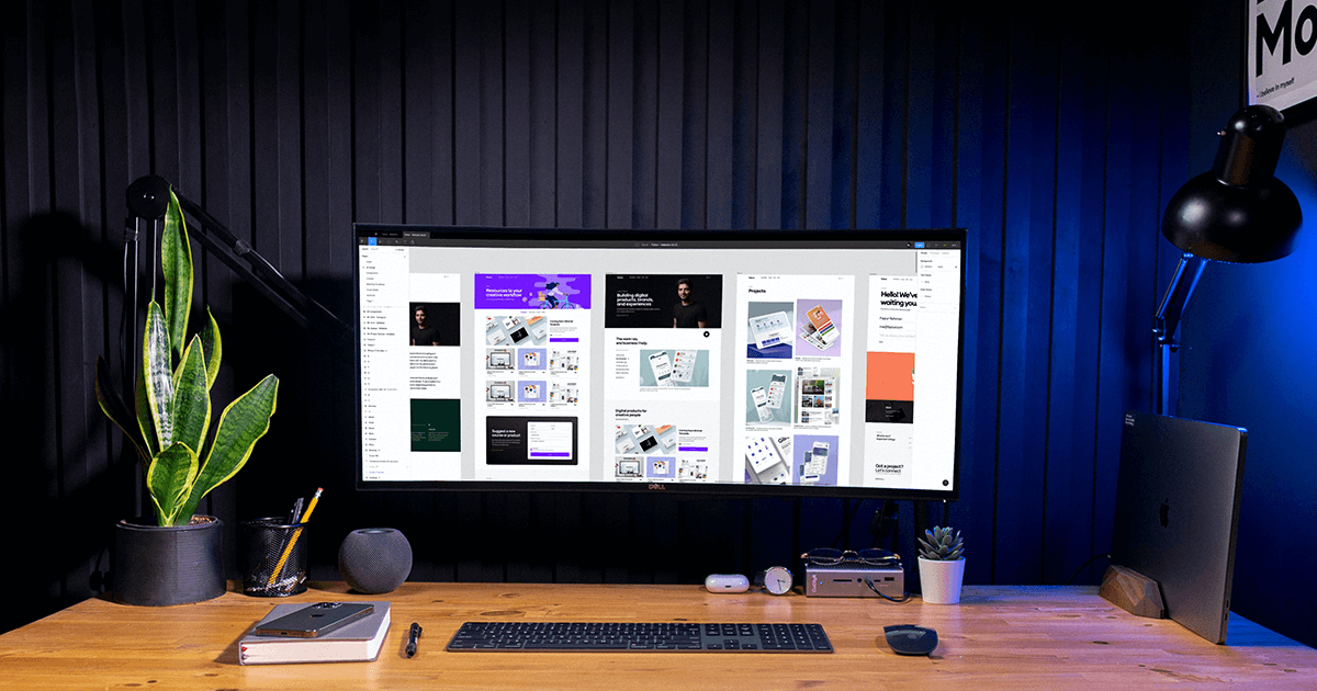 A clean and organized desk with a panoramic monitor. On the screen is a series of related webpage designs. They appear crisp and clean.