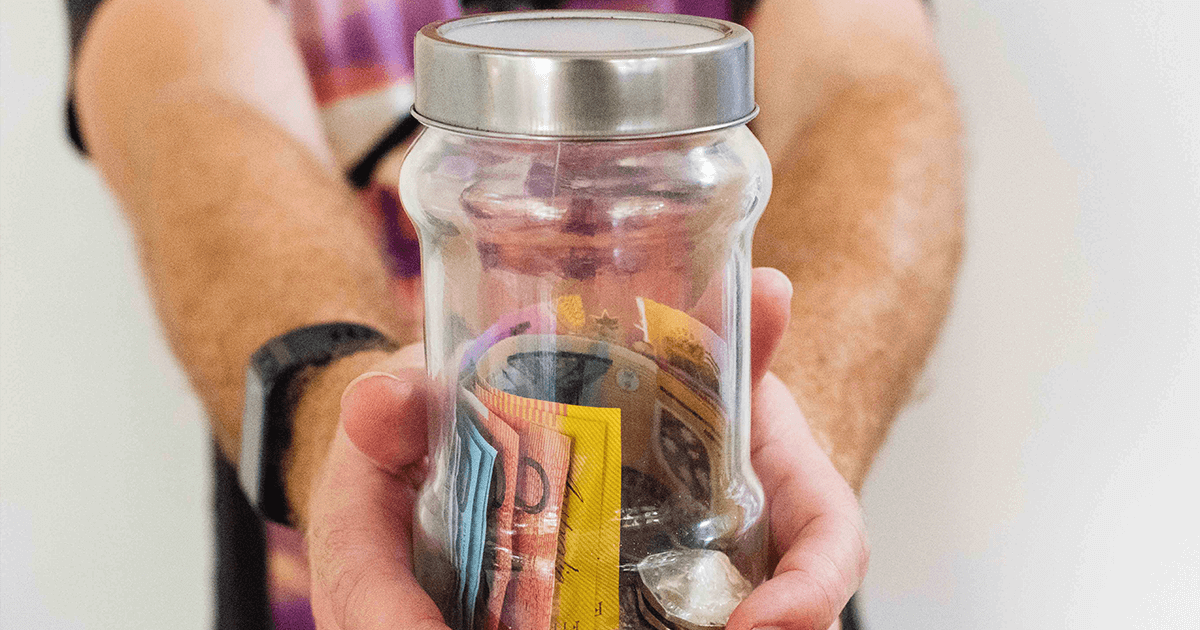 Closeup of a man's hands reaching toward the viewer holding a jar full of colourful money, bills and coins.