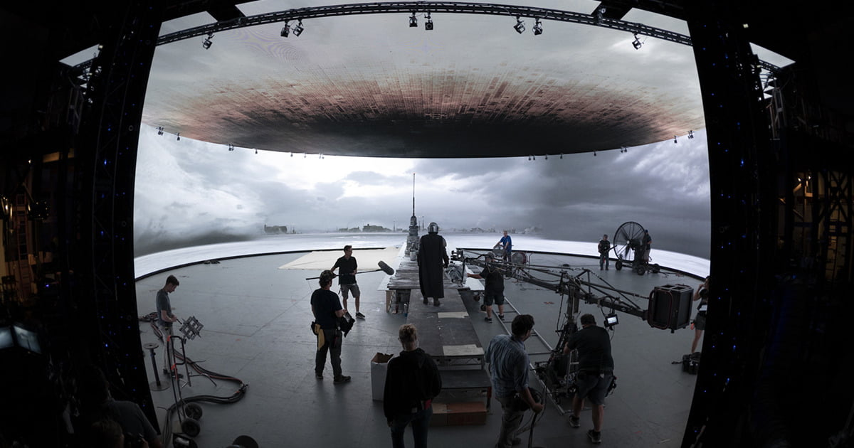 Behind-the-scenes image from the set of Disney's The Mandalorian. Mando and the crew filming in a soundstage surrounded by the giant digital screens of Lucasfilm's StageCraft system.