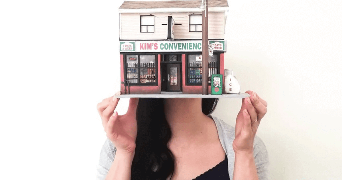 Image of a young woman holding up a model of the Kim's Convenience store in front of her face.